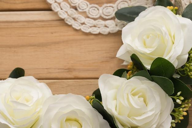 Rosas blancas sobre superficie de madera.
