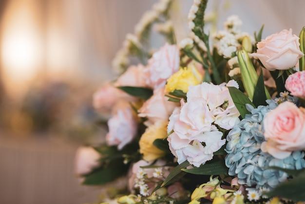 Rosas borrosas y ramo de flores en florero