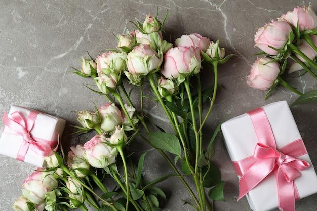 Rosas y cajas de regalo en gris con textura
