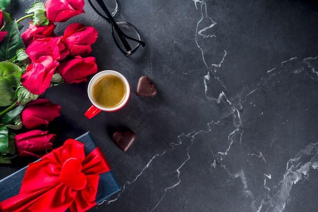 Rosas, calculadora, libreta y vasos en mármol.