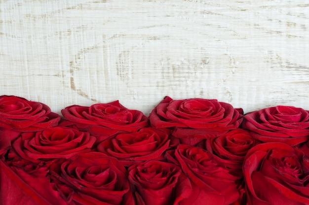 Rosas escarlatas sobre un fondo claro de la madera. de cerca