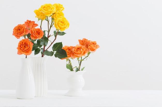 Rosas en florero blanco sobre fondo blanco.