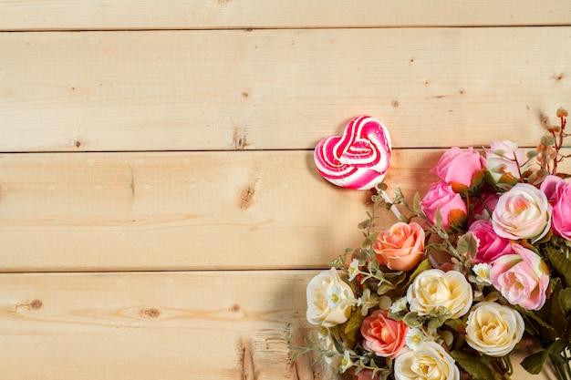 Rosas flores y espacio vacío en la mesa de madera