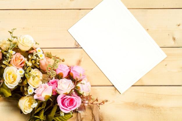 Rosas flores y etiqueta vacía para su texto sobre fondo de madera