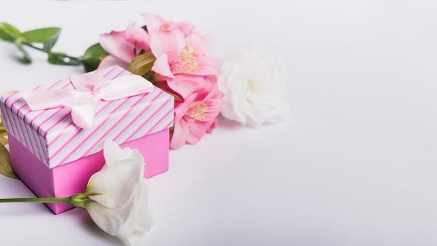 Rosas y flores de lirio rosa con caja de regalo sobre fondo blanco