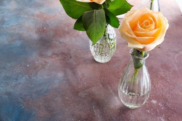 Rosas frescas hermosas del corte del beige en el florero de cristal en el fondo de piedra.