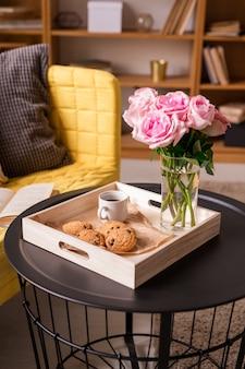 Rosas frescas en un vaso de agua, una taza de café, galletas caseras crujientes en una caja de madera en una mesa pequeña junto a un sofá amarillo con almohadas