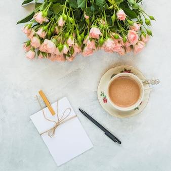 Rosas hermosas; brotes tarjeta de felicitación; taza de café y pluma sobre fondo concreto