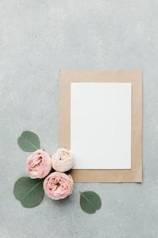Rosas y hojas planas con papeles en blanco y marco