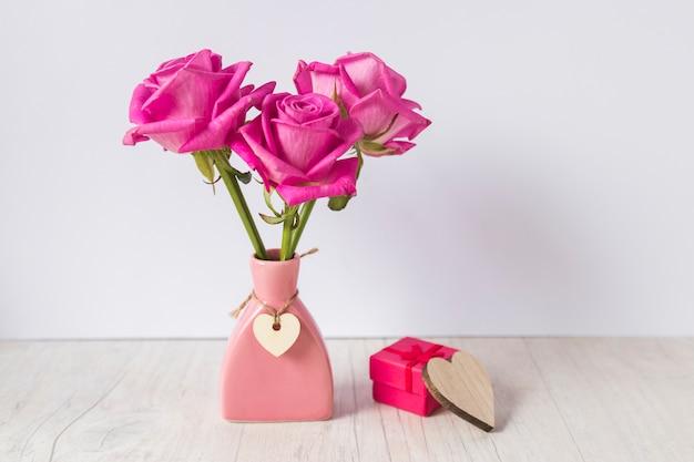 Rosas en jarrón con caja de regalo en mesa de luz.