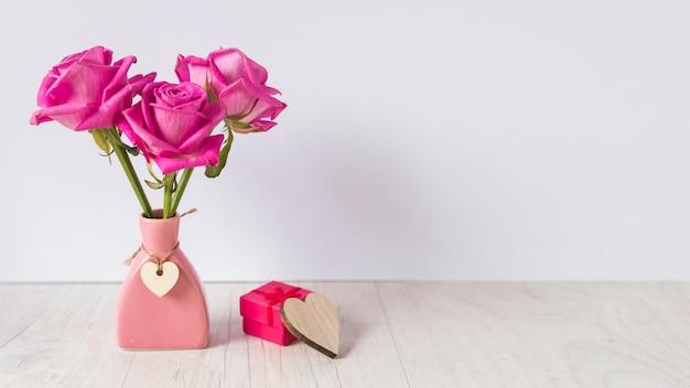 Rosas en jarrón con caja regalo en mesa.