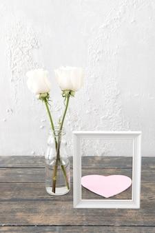 Rosas en jarrón con marco y corazón de papel.