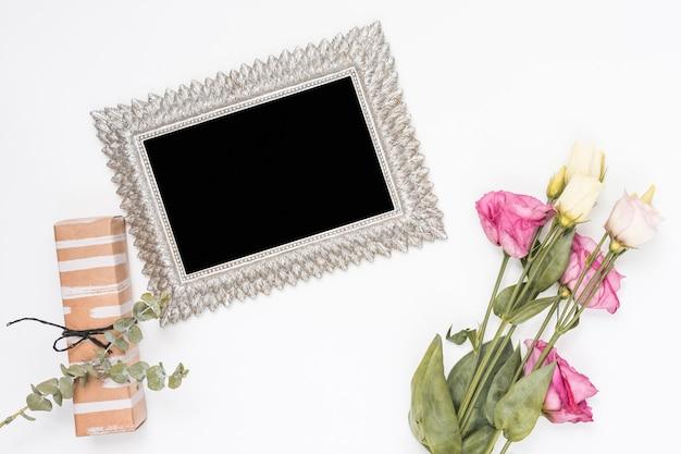 Rosas con marco en blanco y caja de regalo.