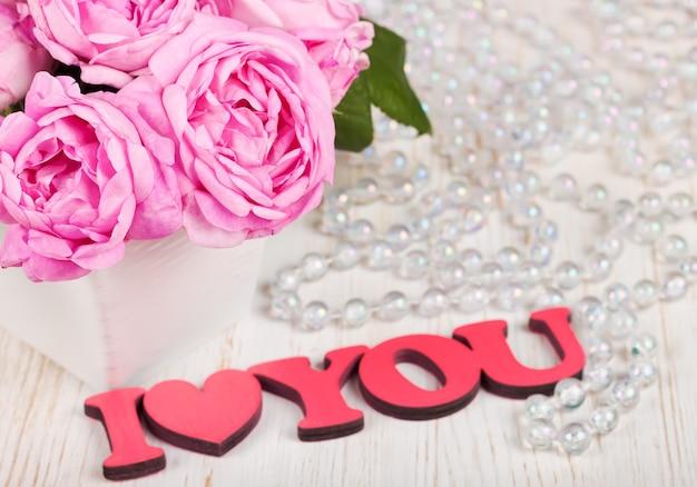 Rosas y pétalos en el escritorio de madera blanco y la palabra de madera roja te amo. concepto de dia de san valentin