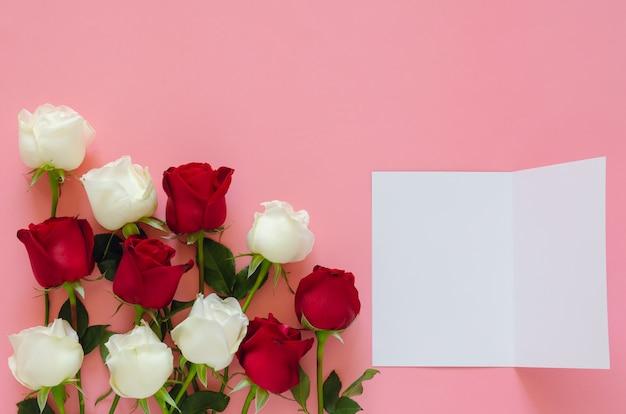 Rosas rojas y blancas sobre fondo rosa con tarjeta blanca vacía para el día de san valentín