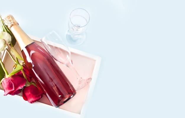 Rosas rojas y botella de vino con copas en la bandeja. vista superior