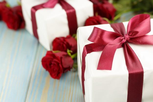 Rosas rojas y caja de regalo en mesa de madera azul claro.