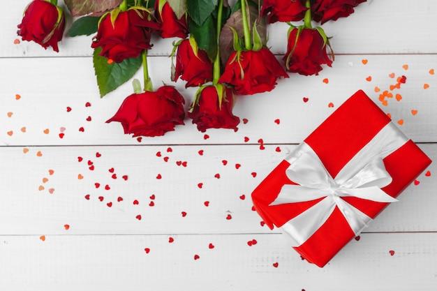Rosas rojas y caja de regalo en mesa de madera