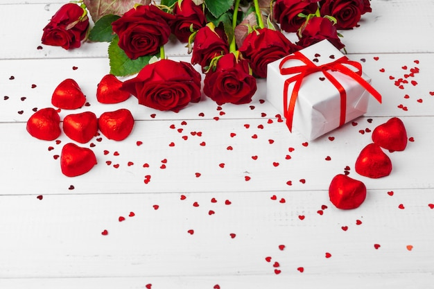 Rosas rojas y caja de regalo en mesa de superficie de madera