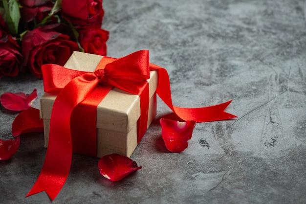 Rosas rojas y caja de regalo sobre fondo oscuro
