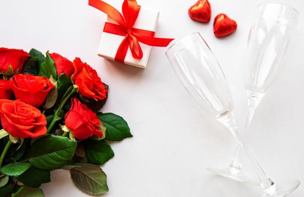 Rosas rojas, caja de regalo y vasos.