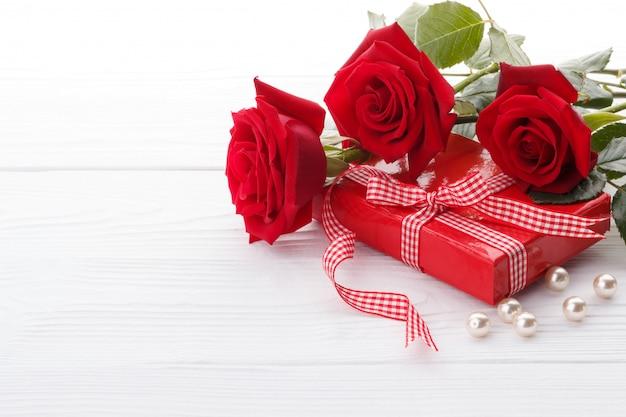 Rosas rojas y una caja de regalo.