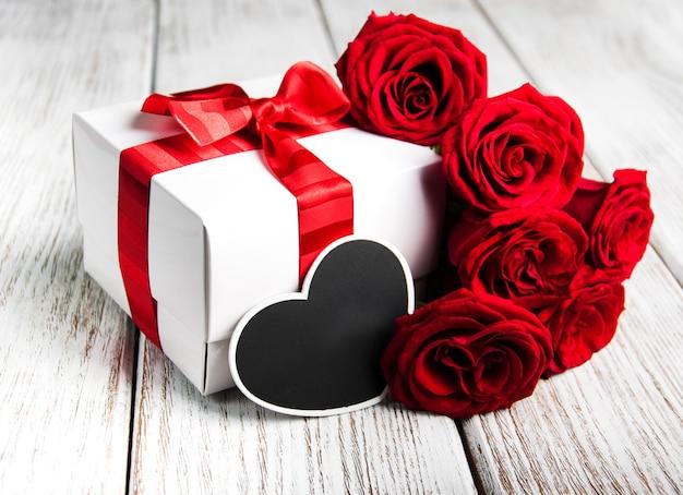 Rosas rojas y caja de regalo.