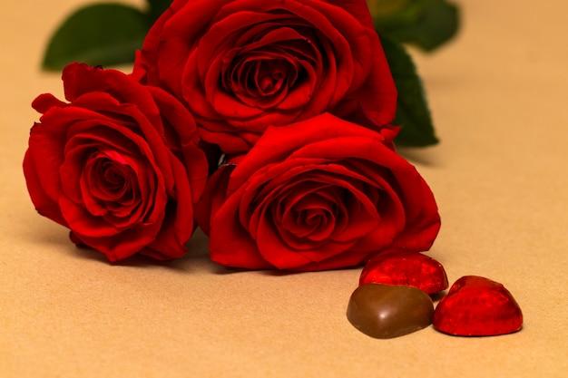 Rosas rojas y corazones sobre un fondo amarillo. fondo del dia de san valentin