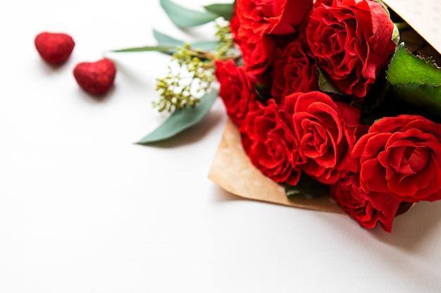 Rosas rojas con eucalipto sobre fondo blanco.