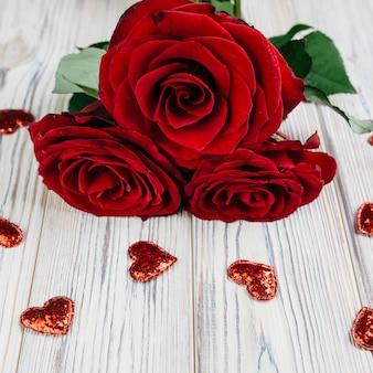 Rosas rojas con pequeños corazones en mesa.