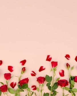Rosas rojas y pétalos copia espacio