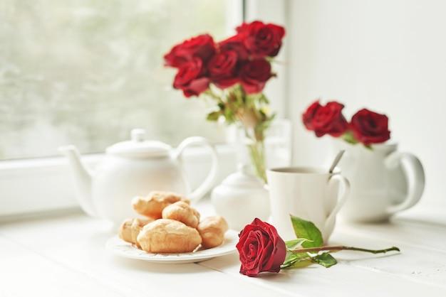 Rosas rojas, té y cruasanes en una mesa cerca de la ventana, desayuno romántico para el día de san valentín