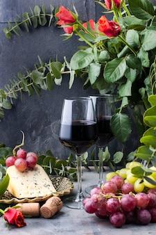 Rosas rojas, uvas, queso y una copa de vino tinto sobre un fondo de hormigón negro