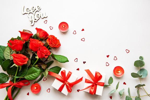 Rosas rojas, velas y cajas de regalo.