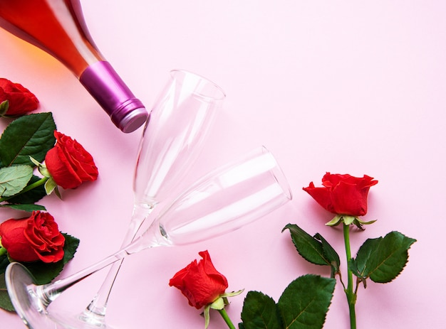 Rosas rojas, vino y copas para vino en rosa claro