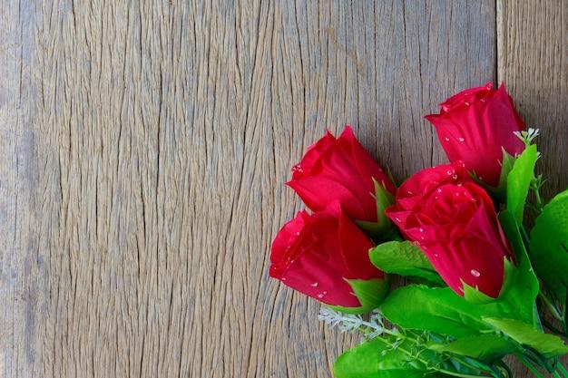 Rosas rojas y sobre fondo de madera. vista superior con espacio de copia, conceptos de san valentín.