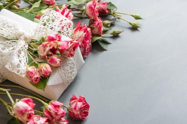 Rosas rosadas del arbusto y regalo femenino en gris