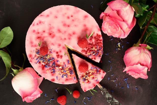 Rosas rosadas y delicioso pastel de frambuesas con bayas frescas, romero, flores secas. vegetariana, concepto de comida vegana.