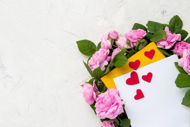 Rosas rosadas están alineadas alrededor de un libro amarillo, sábana blanca