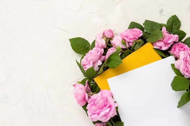 Las rosas rosadas están alineadas alrededor de un libro con una cubierta amarilla sobre un fondo claro.