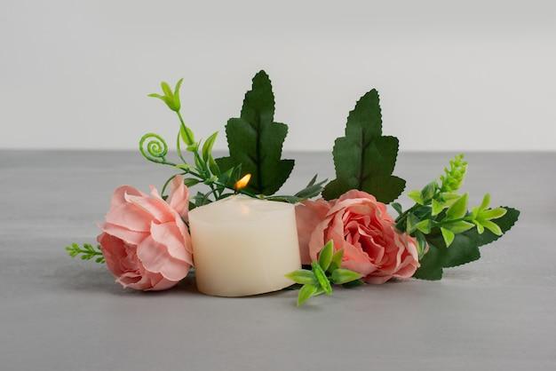 Rosas rosadas con hojas verdes y velas en mesa gris.