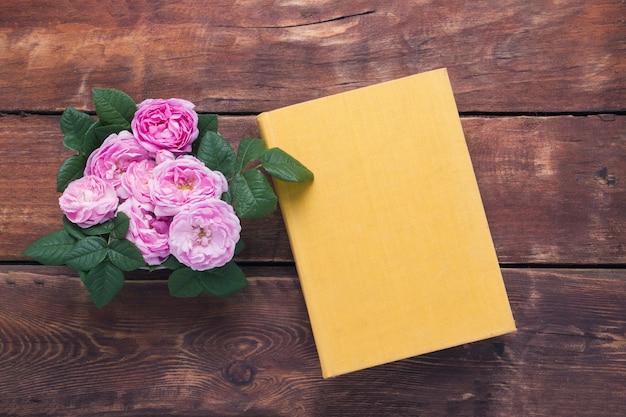 Rosas rosadas y libro con una cubierta amarilla sobre un fondo de madera