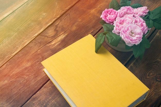 Rosas rosadas y libro con una cubierta amarilla sobre una superficie de madera
