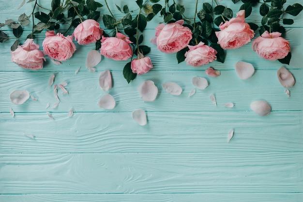 Rosas rosadas en una mesa azul, concepto de verano