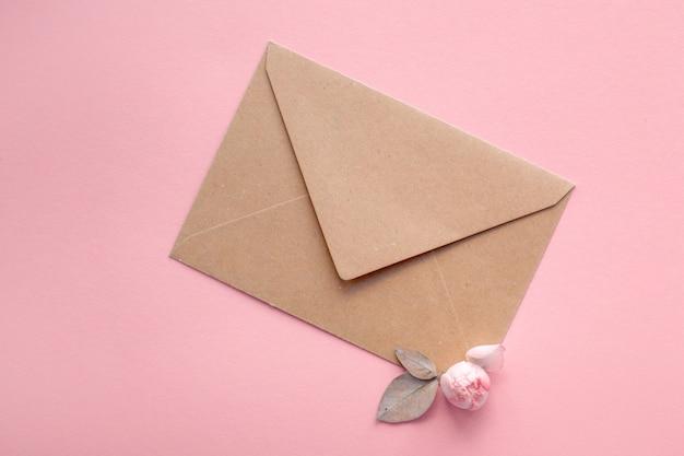 Rosas rosadas en un sobre de papel kraft sobre un fondo rosa pálido