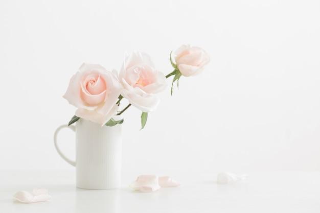 Rosas rosadas en taza blanca sobre mesa de madera blanca