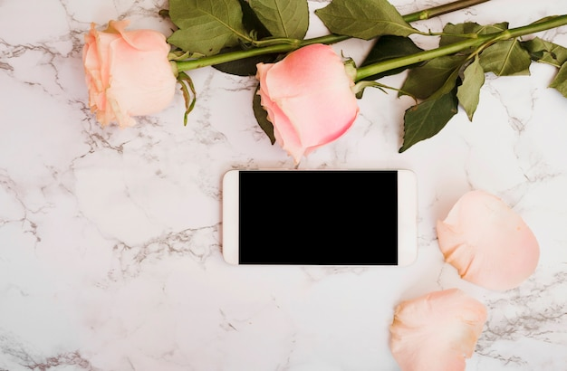 Rosas rosadas con teléfono inteligente en mármol con textura de fondo
