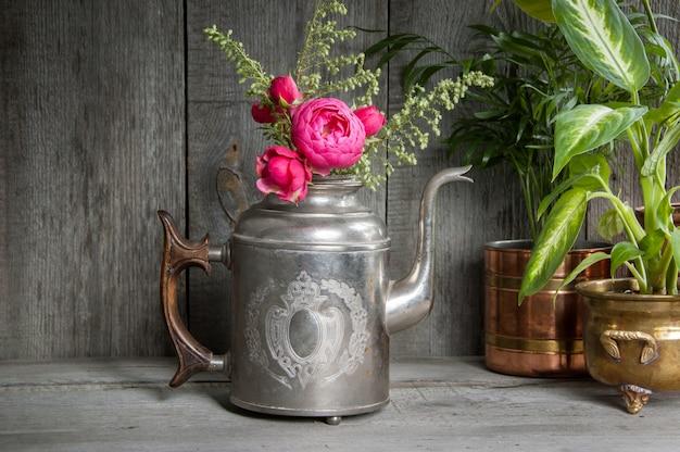Rosas rosadas en tetera de plata vieja y plantas verdes