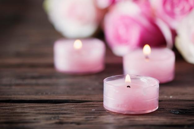 Rosas rosadas y velas pinl en la mesa de madera