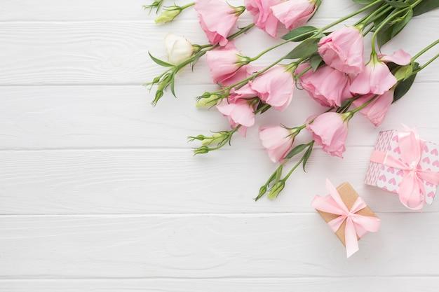 Rosas rosas y cajas de regalos sobre fondo de madera